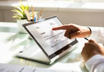 106572805-close-up-of-a-businessman-s-hand-examining-invoice-on-laptop